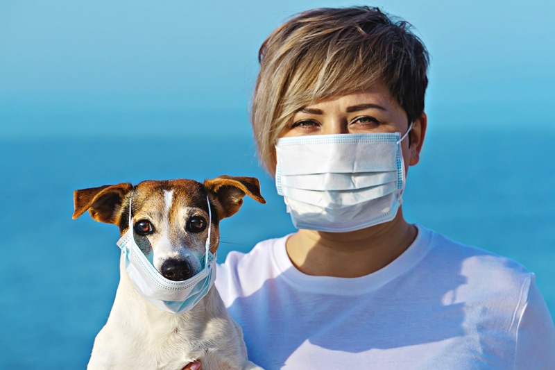 Woman and dog wearing a face mask